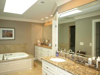Master bath features off-set his and her vanities, a big whirlpool tub, a skylight that floods the room with nature light while keeping the room private and a toilet room that is hidden behind the mirror.