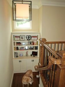 Book shelf tucked into space at the landing. The window above keeps the stairway brightly lit.