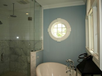The soaking tub is her retreat but the marble and glass shower with multiple heads is his.