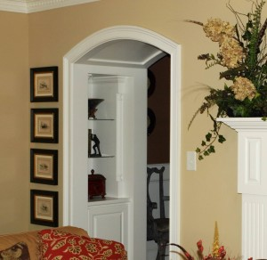 Barrel vaulted arch with storage and display cabinetry. Created in thick wall housing the fireplace.