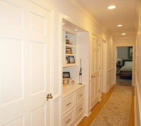 Shelving and cabinets break up and add interest in a long hallway.