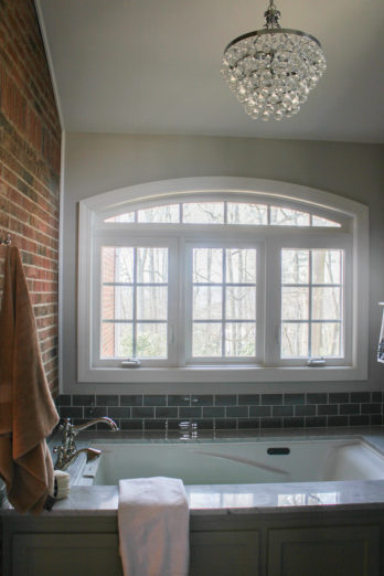 A massive window above the tub lets in sunshine and the original exterior brick wall was kept for character.