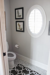 A toilet room is across from the tub with a cute little oval window for some natural light.